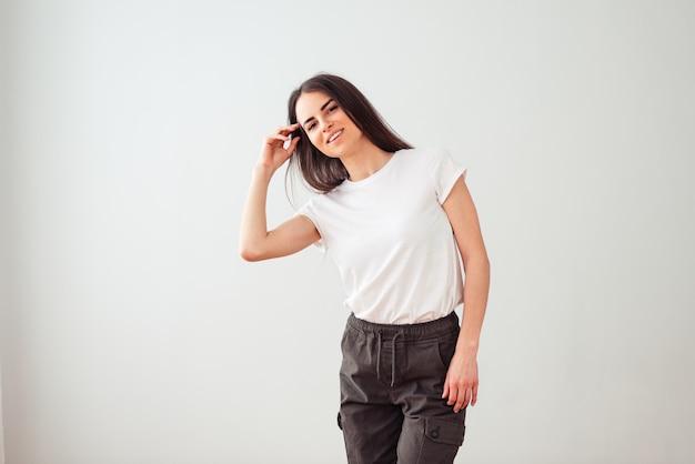 Morena envergonhada com um sorriso lindo em uma mão de camiseta branca alisa o cabelo sobre um fundo claro com lugar vazio para texto