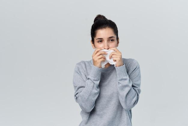 Morena enxuga o nariz com um lenço escorrendo pelo nariz com aparência doentia