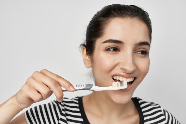 Morena escovar os dentes com uma escova de dentes isolada no fundo