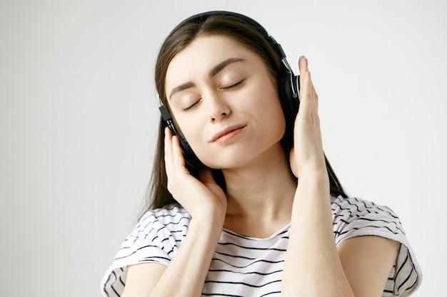 Morena estudante mulher posando com os olhos fechados, ouvindo calmos sons meditativos da natureza ou faixas ambientais usando fones de ouvido