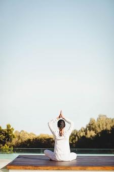 Morena fazendo yoga ao lado da piscina