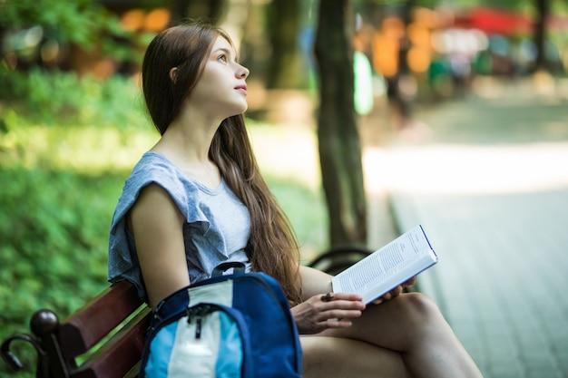 Morena feliz com um caderno nas mãos, sentada em um banco do parque