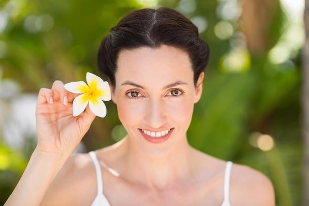 Morena feliz segurando uma flor branca