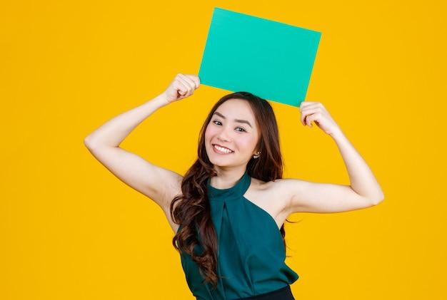 Morena feminina asiática de cabelo bonito e muito encaracolado segurando a placa em branco verde posa para a câmera com um gesto alegre e positivo para fins de uso publicitário, estúdio tiro isolado em fundo amarelo.