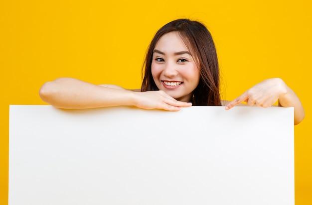 Morena feminina asiática de cabelo bonito e muito encaracolado segurando e apontando para poses de quadro em branco branco para a câmera com uma alegria para fins de publicidade e banner, isolado em fundo amarelo brilhante