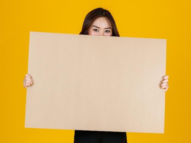Morena feminina asiática de cabelo bonito e muito encaracolado segurando poses de placa em branco marrom para a câmera com uma alegria para fins de publicidade e banner uso, estúdio tiro isolado em fundo amarelo brilhante.