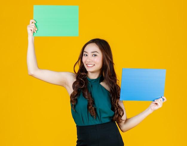 Morena feminina asiática de cabelo bonito e muito encaracolado segurando poses de placa em branco verdes e azuis para a câmera com uma alegria para fins de uso de publicidade, estúdio tiro isolado em fundo amarelo.