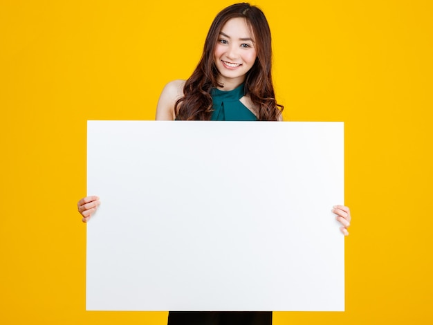 Morena feminina asiática de cabelo bonito e muito encaracolado segurando uma placa em branco branca posa para a câmera com uma alegria para fins de publicidade e banner, tiro do estúdio isolado no fundo amarelo brilhante.