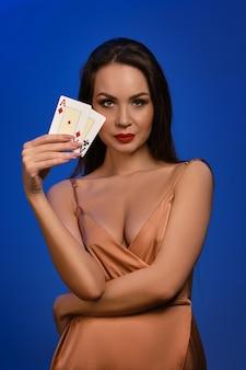 Morena feminina com vestido de seda dourado, sorrindo, mostrando duas cartas de jogar, posando na parede azul