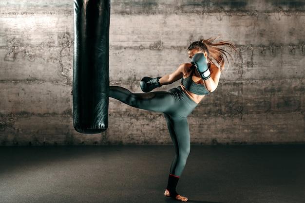 Morena forte dedicada com rabo de cavalo, em roupas esportivas, pés descalços e com luvas de boxe chutando saco no ginásio.