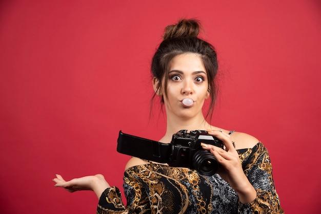 Morena fotografia menina mascando chiclete e verificando o histórico da foto.