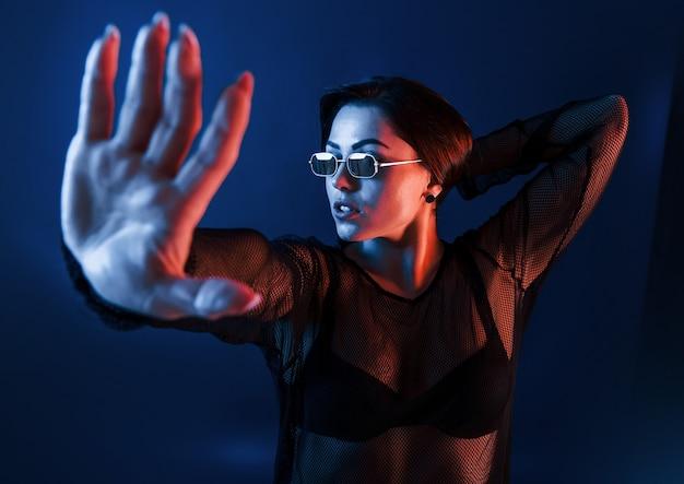 Morena gostosa em óculos de sol posando no estúdio com iluminação neon.