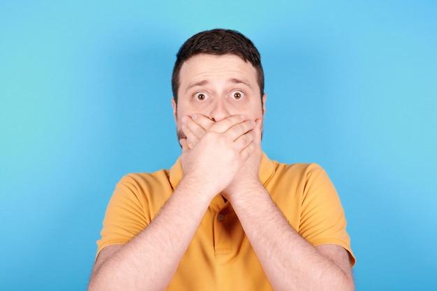 Morena homem assustado, mantém as mãos sobre a boca. isolado em fundo azul