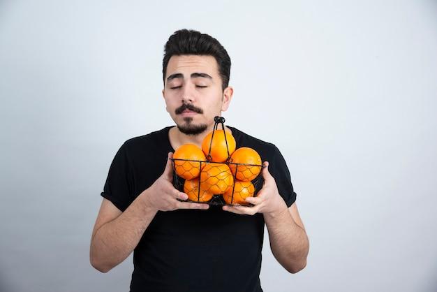 Morena homem modelo em pé e segurando uma cesta metálica com frutas laranja.