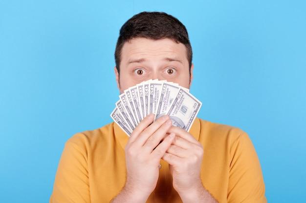 Morena homem segurando a pilha de papel-moeda, emoção chocada. isolado em fundo azul