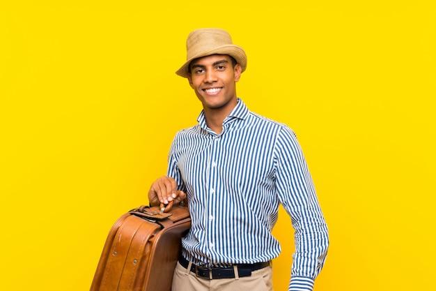 Morena homem segurando uma mala vintage sobre amarelo isolado