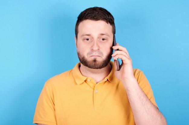 Morena homem usando telefone celular e assustado. isolado em fundo azul