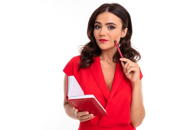 Morena inteligente em um vestido vermelho contra uma parede branca com um caderno nas mãos