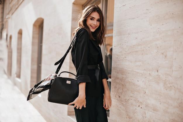 Morena jovem alegre com cabelos fofos, lábios vermelhos, vestido da moda e jaqueta preta, cinto na cintura em pé de perfil na rua ensolarada e sorrindo contra a parede do prédio de luz