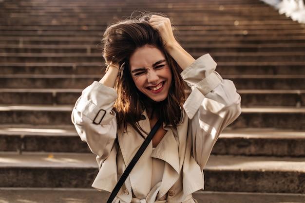 Morena jovem alegre com capa impermeável bege posando, fechando os olhos, balançando o cabelo com as mãos e se divertindo no muro das escadas da cidade velha ao ar livre