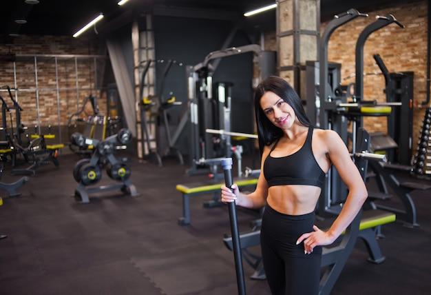 Morena jovem alegre no sportwear com barra de corpo de ginástica na mão e olhando para a câmera no ginásio