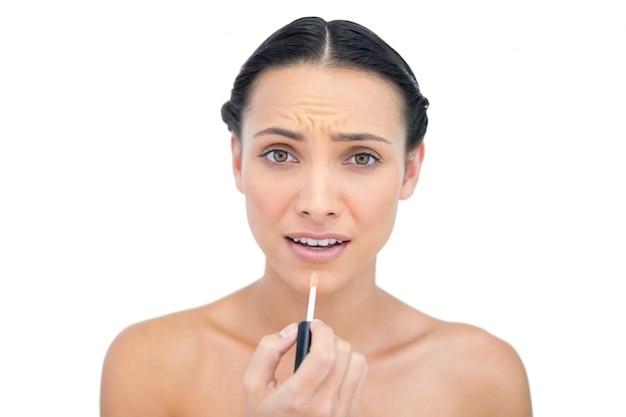 Morena jovem aplicando brilho labial