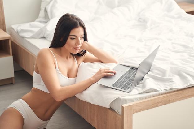 Morena jovem atraente em lingerie elegante, sentada no chão e usando o laptop na cama