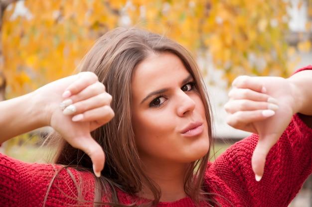 Morena jovem atraente em vermelho mostrando os polegares para baixo em parque público