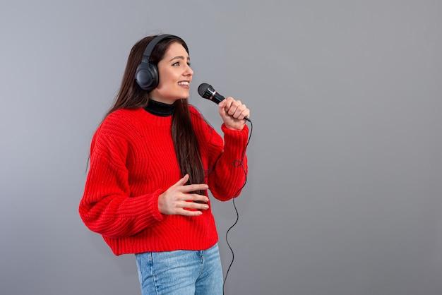 Morena jovem e emocional com fones de ouvido e um microfone vestida com um suéter vermelho canta karaokê, isolado no cinza