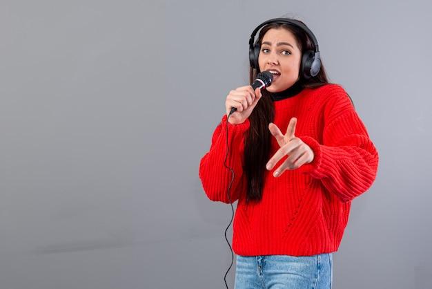 Morena jovem e emocional com fones de ouvido e um microfone vestida com um suéter vermelho canta no karaokê, isolado no cinza