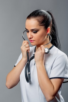 Morena jovem enfermeira sozinha ouvindo com estetoscópio e olhando para baixo.