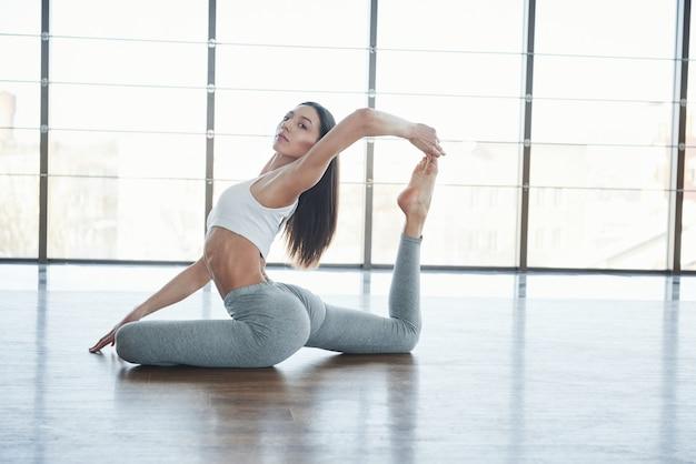 Morena jovem europeia fazendo yoga na sala com grandes janelas