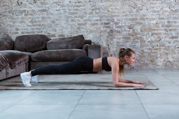 Morena jovem magro, vestindo roupas de ginástica preta fazendo ponte abdominal ou exercício de prancha frontal no apartamento loft.