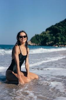 Morena jovem sexy, posando de joelhos no mar