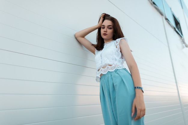 Morena jovem urbana europeia em uma blusa de renda elegante em uma calça azul elegante repousa ao ar livre perto de uma parede branca vintage. menina bonita relaxa ao ar livre num dia de verão. nova coleção.