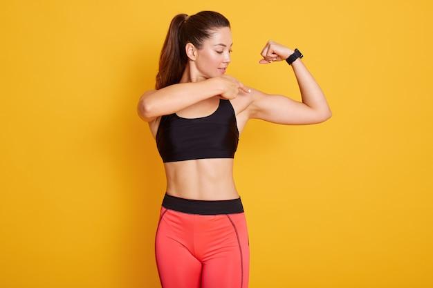 Morena jovem veste top preto e leggins, apontando para o bíceps.