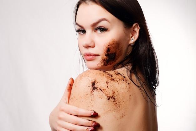 Morena limpa a pele da parede branca do café esfoliante.