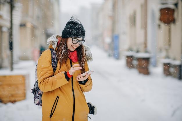 Morena linda alegre na moda de inverno segurando o smartphone na rua urbana