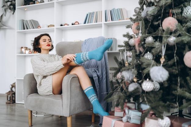 Morena linda com um suéter quente em casa