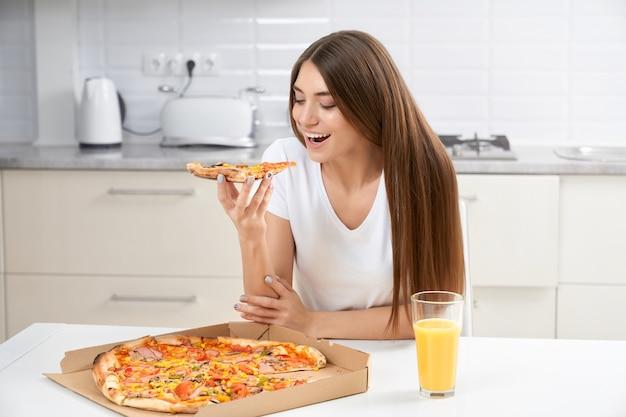 Morena linda comendo pizza em casa
