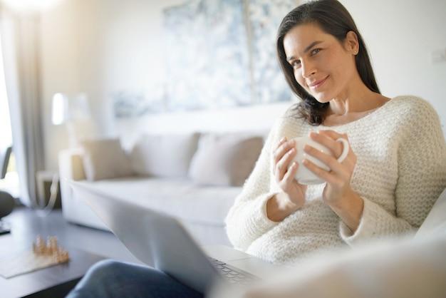 Morena linda descontraída com laptop em casa