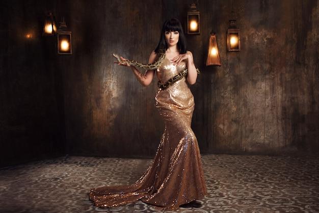 Morena linda e misteriosa em um vestido de ouro e com uma cobra