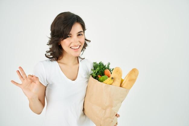 Morena linda em um pacote de camiseta branca com supermercado de verduras e legumes