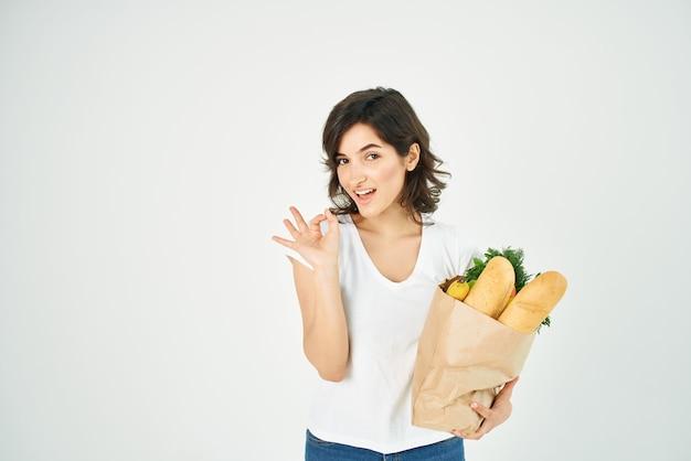 Morena linda em um pacote de camiseta branca com supermercado de verduras