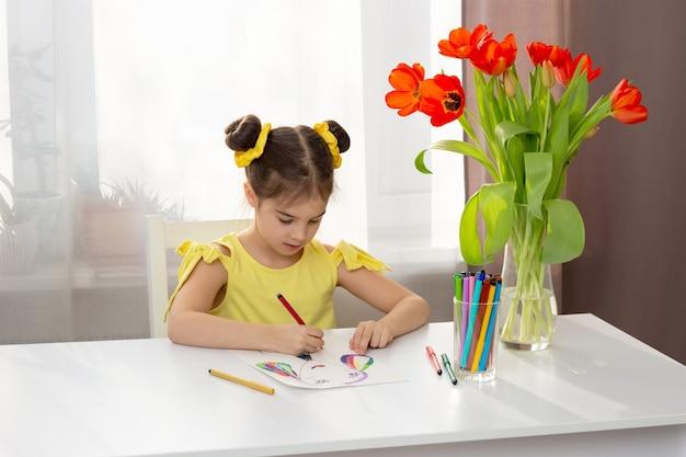 Morena linda em um vestido amarelo desenhando com marcadores coloridos na mesa branca em casa