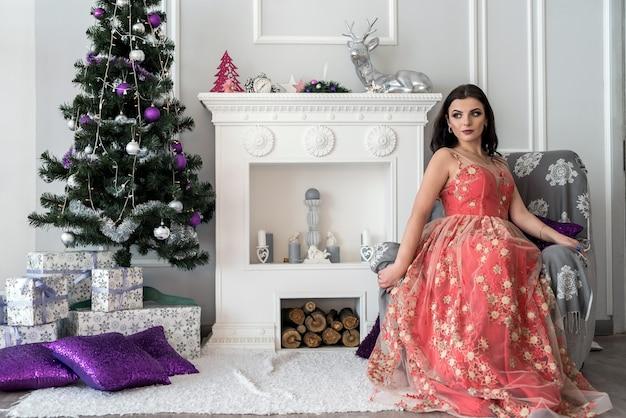 Morena linda em um vestido incrível posando perto da lareira