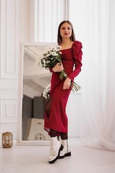 Morena linda em um vestido vermelho com um buquê de margaridas em casa