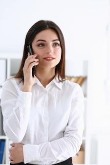 Morena linda empresária falando ao telefone no escritório