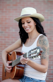Morena linda mulher tocando uma guitarra