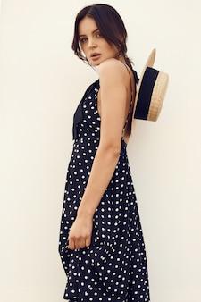 Morena linda no vestido da moda com chapéu posando contra uma parede branca